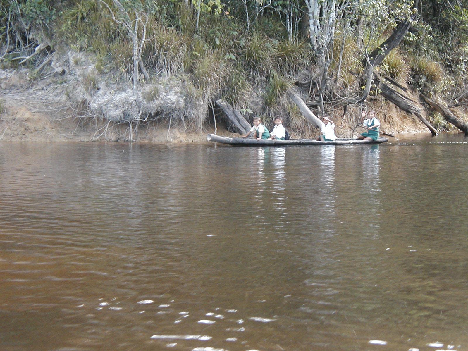 Jawalla schoolchildren on their way to school in a woodskin canoe