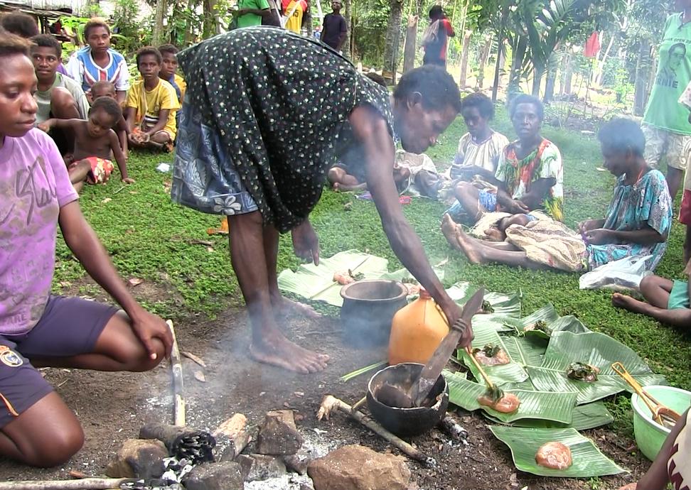 Serving sago and greens onto banana leaves.