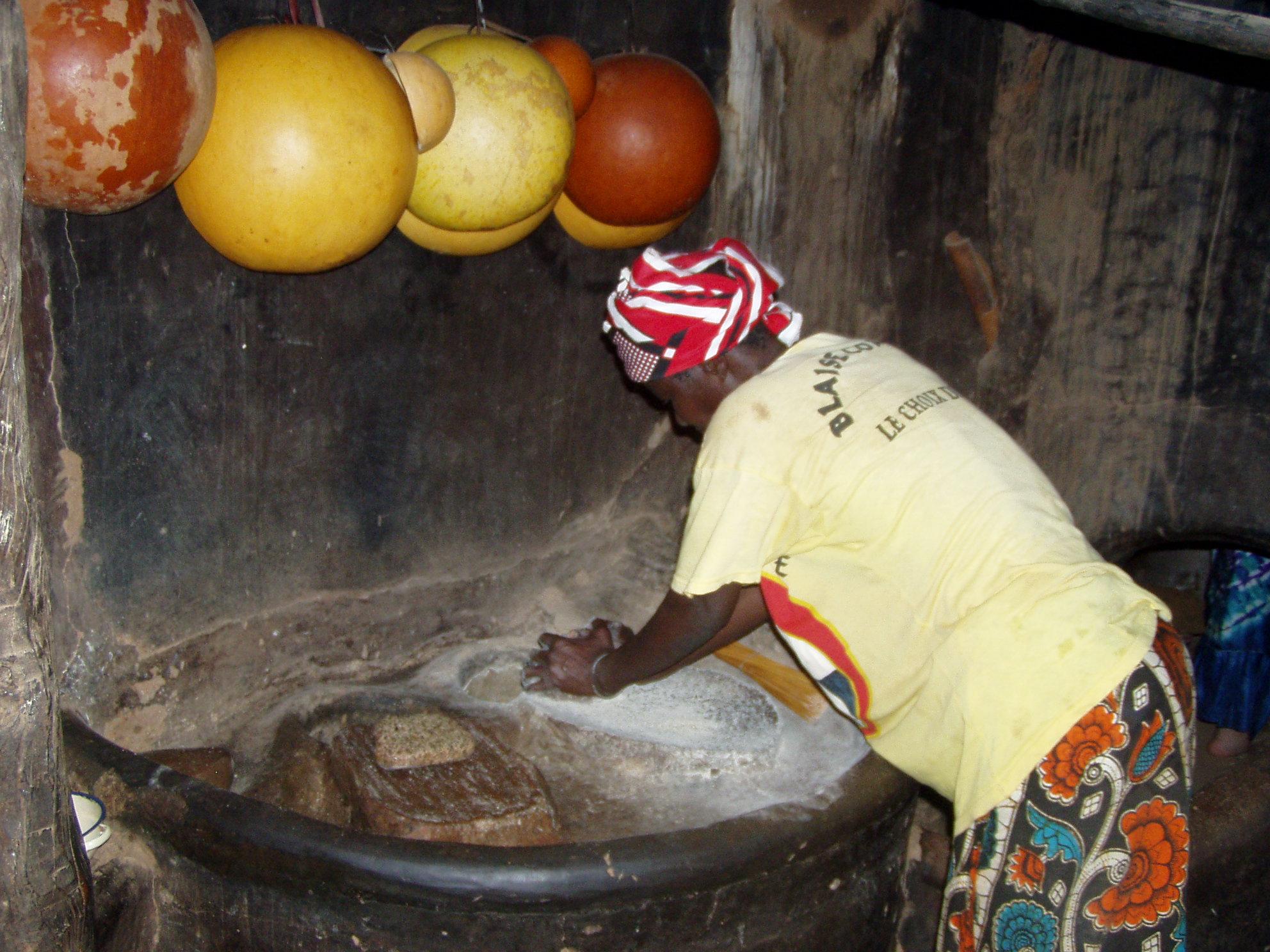 Femme en train de moudre du mil. Lady grinding millet.